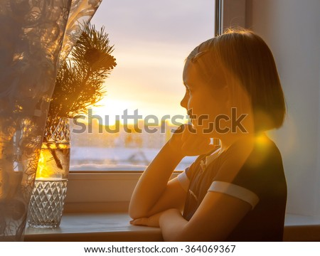 The happy girl at a window in beams of a rising sun - stock photo