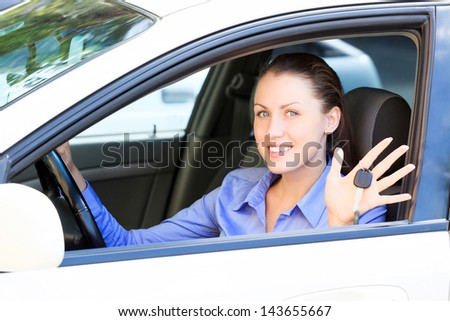The happy girl showing the key of her new car - stock photo