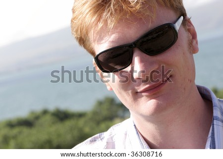 The happy red-haired man poses outdoor in summer - stock photo