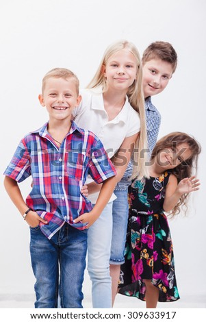The  happy smiling teenagers standing arm in arm on white background. - stock photo