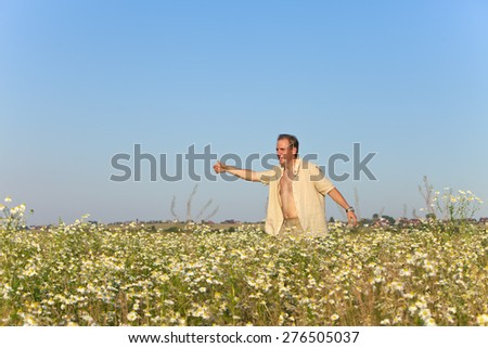 The happy young man  in the field of camomiles - stock photo
