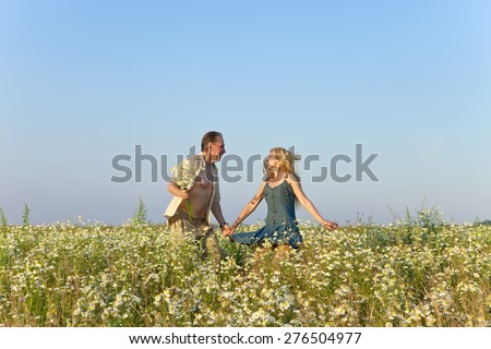 The happy young pair in the field of chamomiles jumps - stock photo