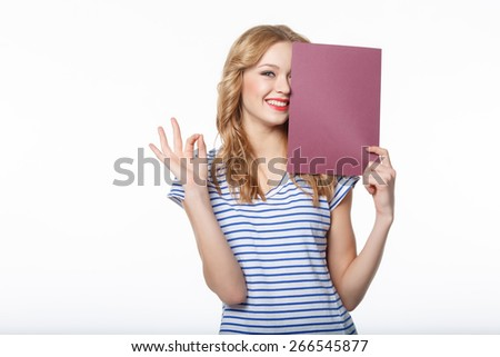 The happy young woman holding a pure billboard and showing OK on a white background - stock photo
