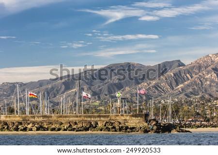 The harbor at Santa Barbara, California.  View from the ocean with Santa Ynez Mountain range and harbor flags  - stock photo