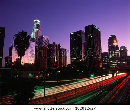 The Harbor Freeway with Los Angeles skyline at night, California - stock photo