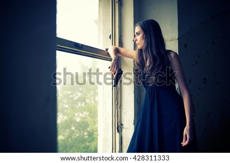 The haunted house. Creepy depressed woman stays in a window, looking outside to the light. There is something paranormal. Cold and freeze atmosphere - stock photo
