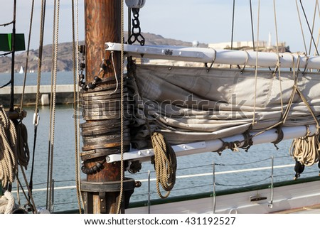 The hawser on the sailboat mast and the square sail - stock photo