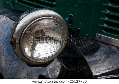 The headlamp on an old truck, with raindrops. - stock photo