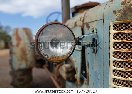 The headlight of abandoned rusty vintage tractor. Small depth of field - stock photo