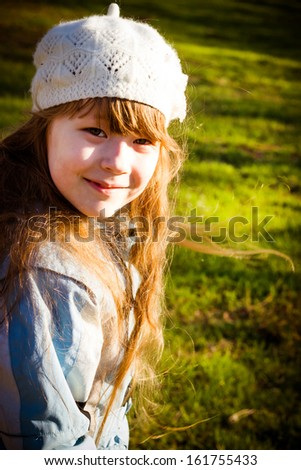 The healthy little girl smiling, walks in park in the autumn - stock photo