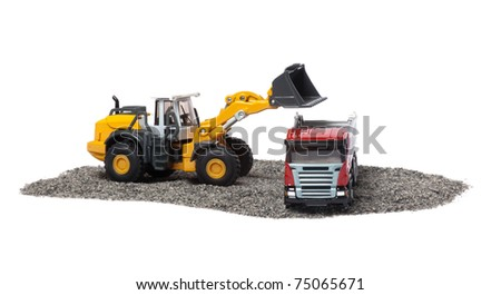 The heavy bulldozer of yellow color on a white background is loading of heavy dump-body truck - stock photo