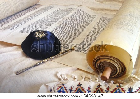 The Hebrew handwritten Torah, on a synagogue alter, with Kippah and Talith  - stock photo