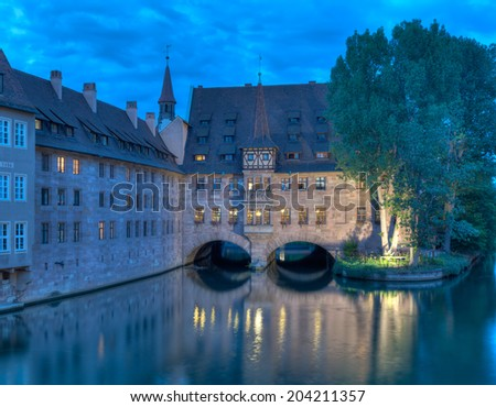 The Heilig-Geist-Spital in Nuremberg, Germany which dates from 1424 on the river Pegnitz - stock photo