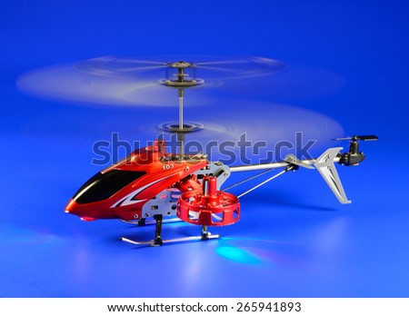 The helicopter radio-controlled for game and entertainment to children and adults on a blue background - stock photo