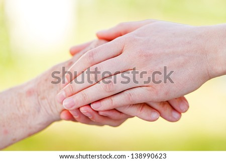 The helping hands for elderly home care - stock photo