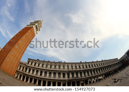 the highest and most famous campanile in Piazza San Marco in Venice photographed with fisheye lens and the immense square - stock photo