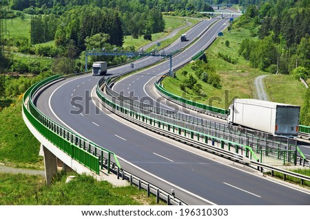 The highway between woods, in the middle of the highway electronic toll gates, three moving trucks, in the distance Bridges - stock photo