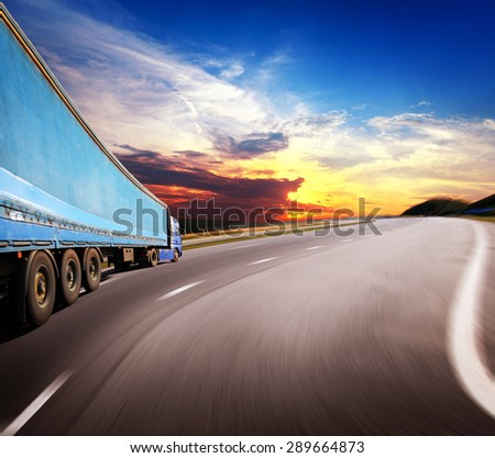 The highway traffic in sunset near fields - stock photo