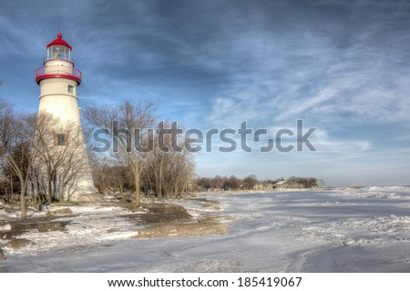 The historic Marblehead Lighthouse in Northwest Ohio sits along the rocky shores of Lake Erie. Seen here from out on the frozen lake where large chunks of ice have piled up near shore. - stock photo