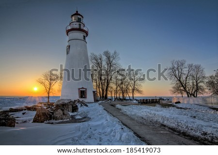 The historic Marblehead Lighthouse in Northwest Ohio sits along the rocky shores of Lake Erie. Seen here at in winter sunrise.  - stock photo