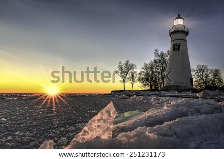 The historic Marblehead Lighthouse in Northwest Ohio sits along the rocky shores of Lake Erie. Seen here in winter at sunrise. - stock photo