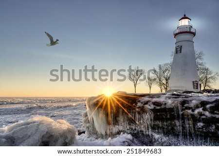 The historic Marblehead Lighthouse in Northwest Ohio sits along the rocky shores of the frozen Lake Erie. Seen here in winter with a colorful sunrise and snow and ice. - stock photo