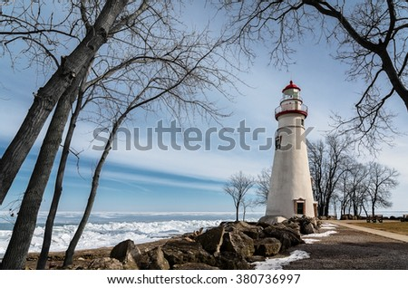 The historic Marblehead Lighthouse in Northwest Ohio sits along the rocky shores of the frozen Lake Erie. Seen here in winter with a colorful sky and snow on the ground. - stock photo