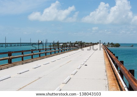 The Historic Seven Mile Bridge in the Florida Keys. In the background is Pigeon Key and the new seven mile bridge. Note the railroad ties from the original Flagler railroad serving as guiderails. - stock photo