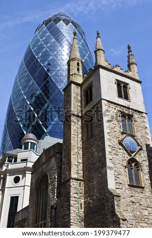 The historic St. Andrew Undershaft Church with 30 St. Mary Axe towering above it in the City of London. - stock photo