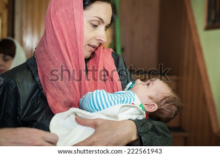 The Holy Orthodox rite of the sacrament of baptism newborn baby in a small wooden Christian Church, Ukraine.Happy christian family. Happy parents with newborn baby in baby in the church - stock photo