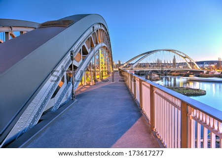 The Honsellbruecke in Frankfurt at early evening with the new Osthafenbruecke behind. - stock photo