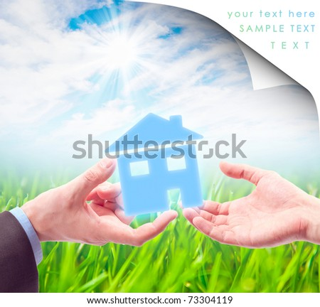 The House in the Hand against the sunny blue sky as a symbol of the real estate business. Collage. - stock photo