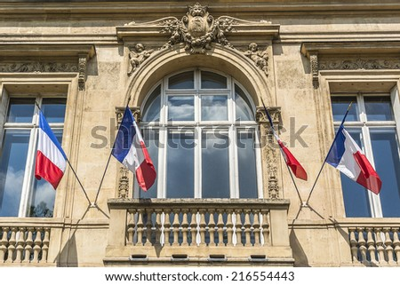 The house on the Champs-Elysees decorated with flags to celebrate the French National Day (Bastille Day). Paris. - stock photo