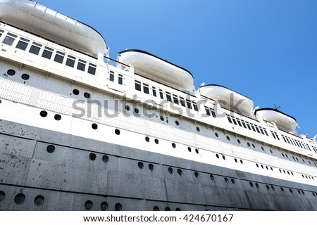 The hull of an old cruise ship shows the puzzled detail of massive metal plates and rivets that make up the ship's main structure - stock photo