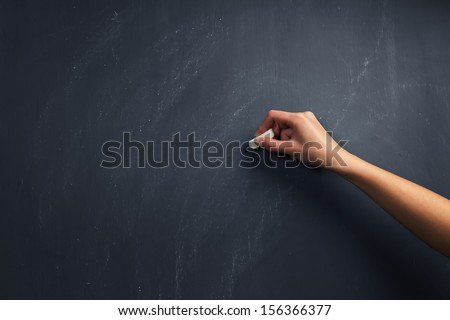 The human hand starts writing with chalk on a clean blackboard - stock photo