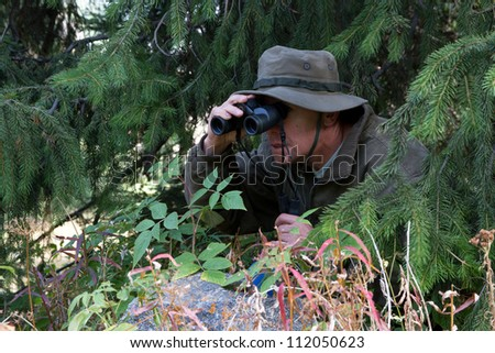 The hunter has hidden among fur-trees and observes in the field-glass - stock photo