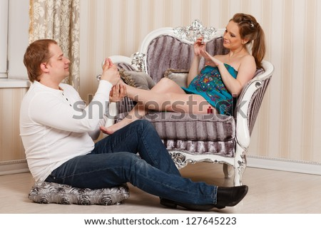 The husband does massage of feet of the pregnant wife of the house. Happy pregnant family. - stock photo