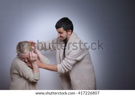 The husband yells at his wife. Family quarrels, violence in the family. Man brandishing his wife. - stock photo