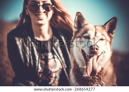 The husky dog outdoor with happy girl behind - stock photo