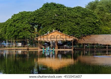 the hut and big Rain tree in garden, Bangkok, Thailand.  - stock photo