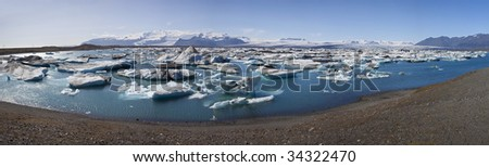 The Iceberg Lagoon, Jokulsarlon, Iceland filled with glacial Icebergs with the Vatnajokull Glacier in the background. Shot in Summer 2009 the lagoon has the greatest number of icebergs for decades. - stock photo