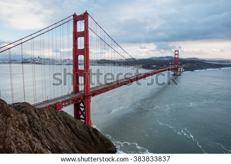 The iconic Golden Gate bridge extends across the San Francisco Bay from the Marin headlands to the beautiful city of San Francisco. The bridge is a symbol of the city and northern California. - stock photo