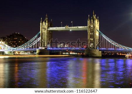 The iconic Tower Bridge of London lit up at night over the River Thames - stock photo