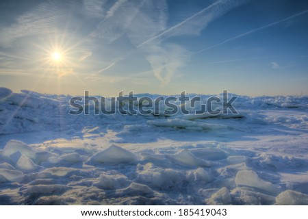 The icy and cold rocky shore of Lake Erie In Northwest Ohio at sunrise.  - stock photo