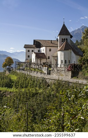 The idyllic little church of St. Peter at Meran shows Romanesque architectural fragments and is a popular hiking destination - stock photo