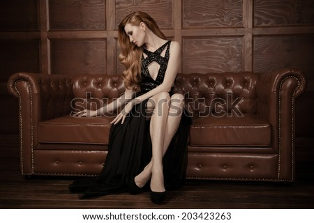 The image of a beautiful luxurious woman sitting on a leather vintage couch. - stock photo