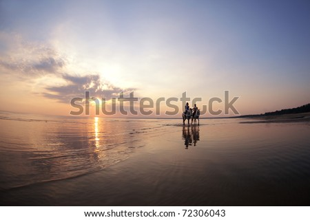 The image of a couple in love at sunset in the sea - stock photo
