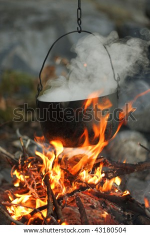 The image of a fire in the woods on which is brewed pot - stock photo