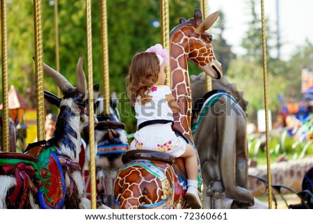 The image of a girl riding on a carousel - stock photo