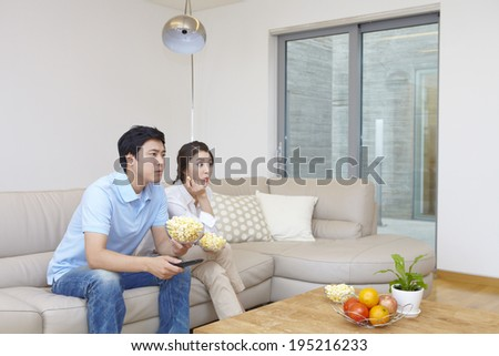 the image of a happy Asian family watching TV - stock photo